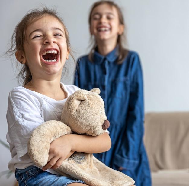 Две сестренки играют с плюшевым мишкой, веселятся дома.