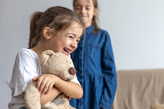 Two little sister girls are playing with a teddy bear, having fun at home.