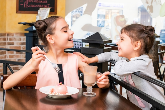 Two little sister girls in a coffee shop