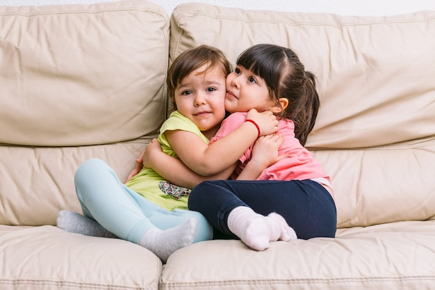 Two little sister girls embracing, sitting on a cream colored sofa