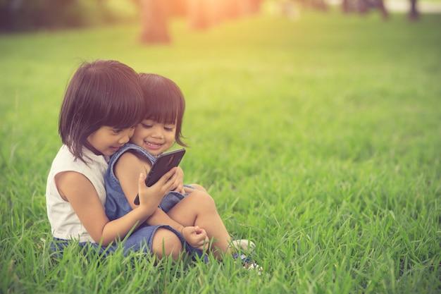 草の上にモバイルスマートフォンでインターネットをしている2人の妹の女の子