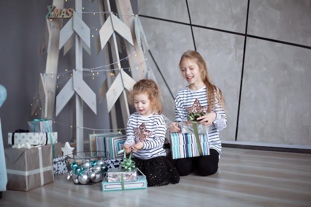 두 명의 작은 자매가 현대 거실에 앉아 크리스마스 선물을보고 있습니다.