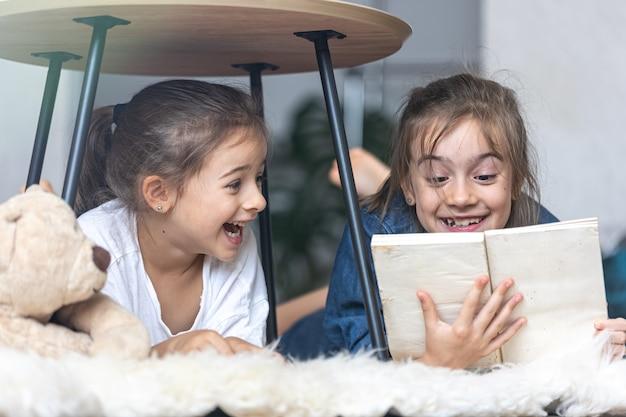 Две сестренки читают книгу, лежа на полу на уютном пледе.