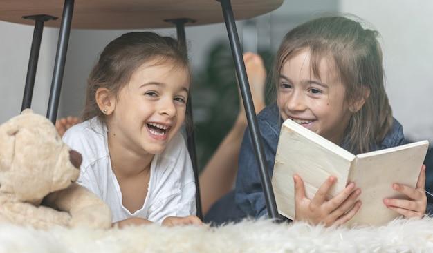 두 명의 여동생이 아늑한 담요를 깔고 바닥에 누워 책을 읽고 있습니다.