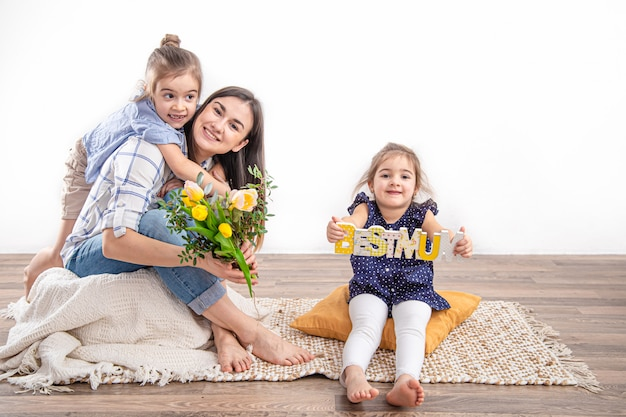 Две сестренки поздравляют маму с днем матери.