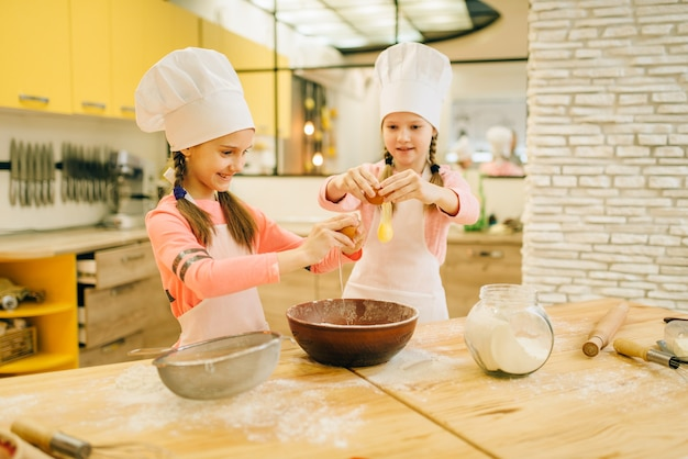 Two little sisters cooks in caps kneads eggs in a bowl, cookies preparation on the kitchen. kids cooking pastry, children chefs makes dough, child preparing cake