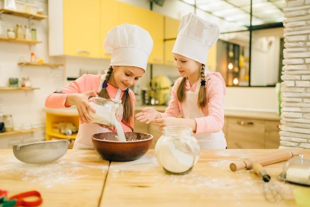 帽子をかぶった二人の妹がボウルに小麦粉を注ぎ、キッチンでクッキーの準備をします。子供たちがペストリーを調理し、子供たちのシェフが生地を作り、子供たちがケーキを準備します