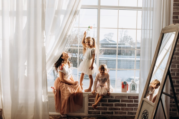 美しいドレスを着た2人の妹と、冬が外にある鏡の横の窓辺に若い母親が座っています。