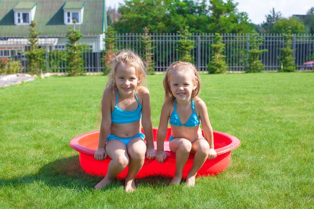 Two little sisters frolicing and splashing in their yard