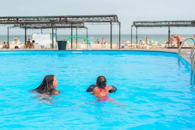 두 명의 여동생이 바다와 해변을 배경으로 호텔 근처에 있는 맑고 푸른 물이 있는 큰 수영장에서 수영을 하고 있습니다. 아이들과 함께 개념 휴가 열대 더운 나라