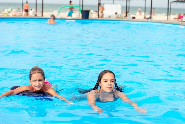 Two little sisters girls are swimming in a large pool in the beach