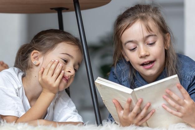Две маленькие сестры весело читают книгу, лежа на полу в своей комнате.