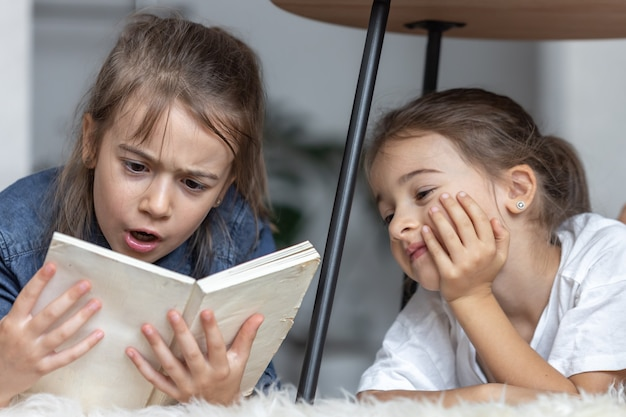 Two little sisters have fun reading a book together while lying on the floor in their room.