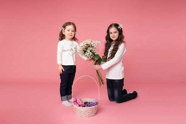 Две сестренки в повседневной одежде с цветами в волосах стоят возле корзины весенних цветов