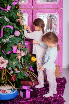 Две маленькие сестры в пижаме украшали елку.