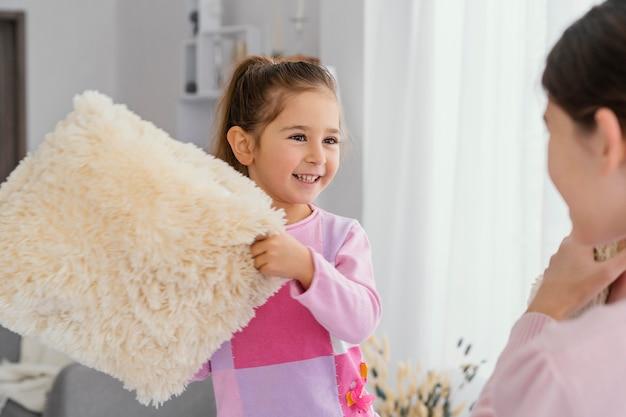 집에서 함께 베개를 가지고 노는 두 명의 작은 자매