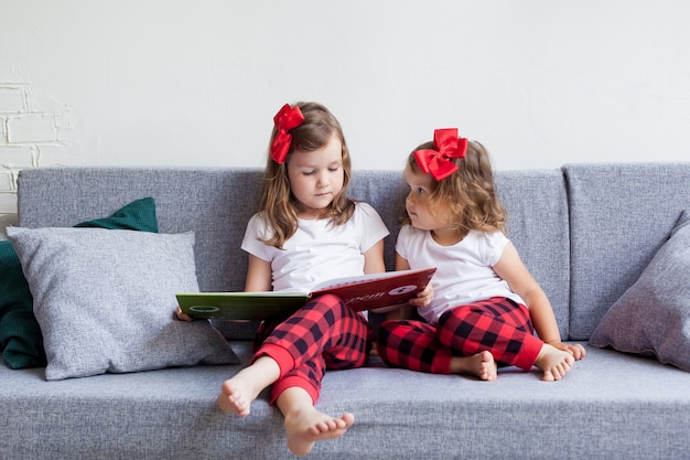 Two little sisters sit together on a sofa on a sunny summer day and read a book.