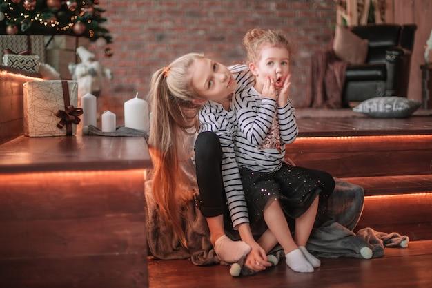 아늑한 거실에 함께 앉아있는 두 명의 작은 자매.