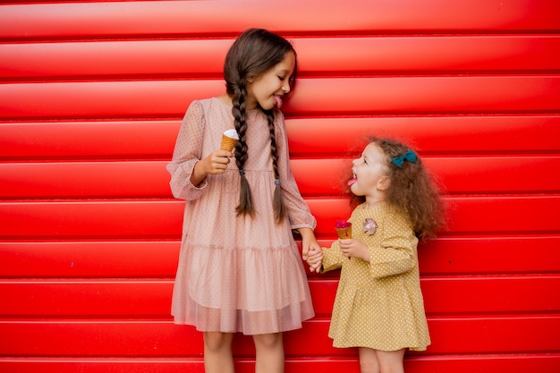 두 명의 여동생이 빨간 울타리에 서서 아이스크림을 먹습니다. 땋은 머리를 한 갈색 머리 소녀와 두 번째 곱슬 머리