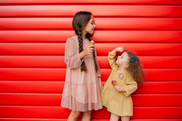 Две сестренки стоят у красного забора и едят мороженое. одна брюнетка с косичками, а вторая кудрявая малышка