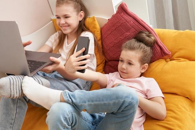 집에서 침대에 누워 노트북을 사용하는 두 여동생