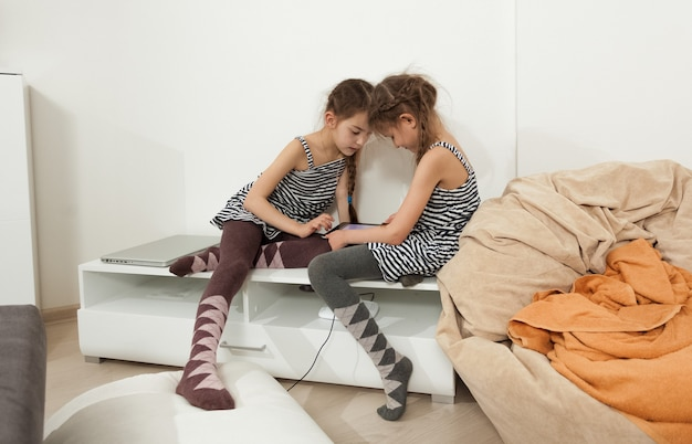 Two little sisters using tablet in bedroom