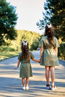 Two little sisters with beautiful hairstyles and identical dresses stand with their backs to the camera.