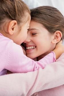 家で一緒に遊んでいる2人の小さな笑顔の姉妹