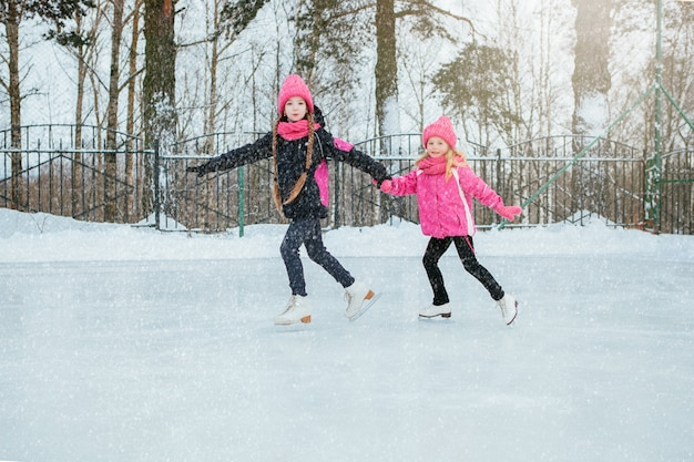 Two little smiling girls skating on ice in pink wear and hand made scarfs.
