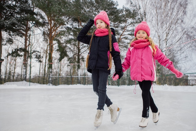 Two little smiling girls skating on ice in pink wear.