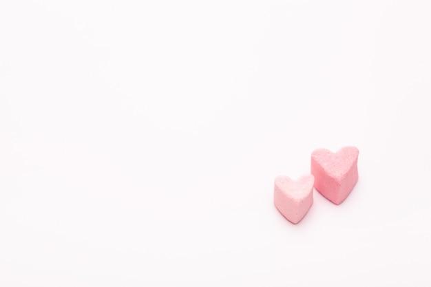 분홍색 배경에 마시 멜로에서 두 개의 작은 달콤한 마음. 행복한 발렌타인. 달콤한 엽서. 텍스트를위한 여유 공간