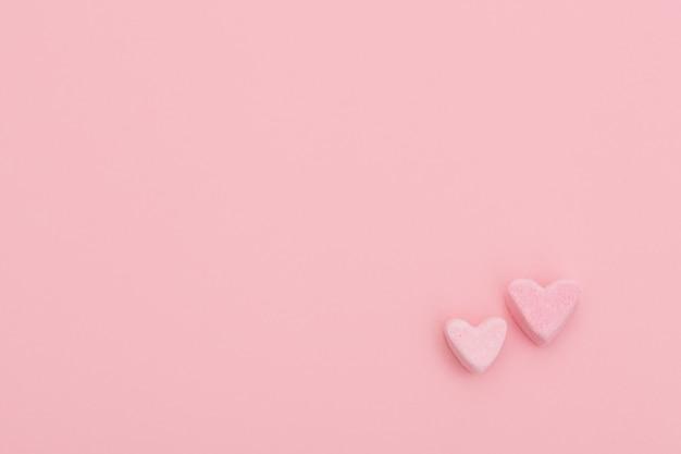 분홍색 배경에 마시 멜로에서 두 개의 작은 달콤한 마음. 행복한 발렌타인. 달콤한 엽서
