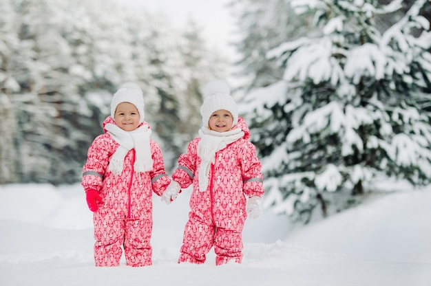 Two little twin girls in red suits stand in a snowy winter forest.