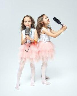 두 명의 작은 쌍둥이 소녀가 빗으로 만든 수제 마이크에 노래