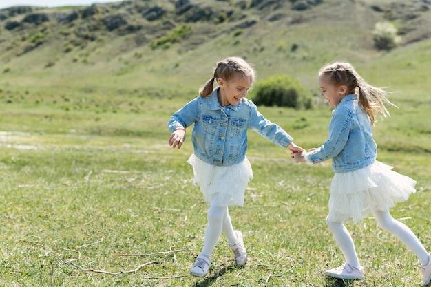 두 명의 작은 쌍둥이 자매가 초원에서 달리고 회전합니다.