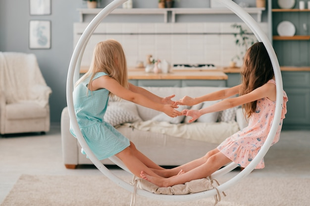 Two little weird girls with long hair covering their faces sitting in swing in children room interior.