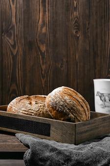 Две буханки цельнозернового пшеничного хлеба ремесленника на деревянном столе