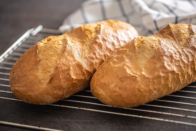 Две буханки горячего хлеба на решетке духовки с полотенцем на заднем плане.