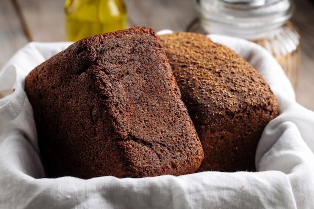 Две буханки ржаного хлеба в корзине с салфеткой