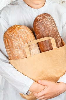 Two loaves of bread in a paper bag in his hands