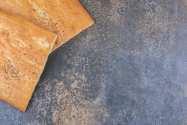 大理石の表面にカリカリに半分スライスしたタンドリーパンの2つのパン