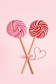 Две конфеты lollipop связаны вместе, красное сердце в день святого валентина. концепция любви. плоская планировка, минимальная.