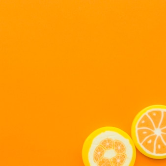 Two lollipops at the corner of orange background