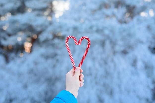 ボケの光のぼやけた背景に赤と白のハートの形をした2つのロリポップ。バレンタインデーの愛。クリスマスのお菓子