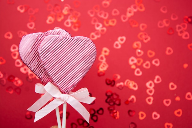 Two lollipops in the shape of heart isolated on red background, with confetti bokeh, copy space.