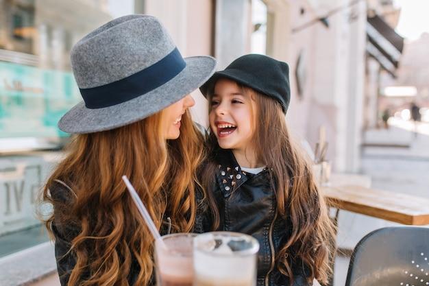 屋外のカフェで晴れた朝を楽しんで、お互いに愛情を込めて探している2人の長髪の巻き毛の姉妹。