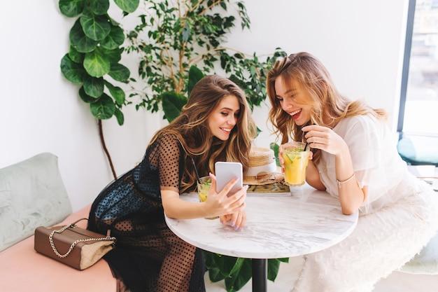 Две длинноволосые девушки отдыхают в кафе с современным интерьером и смеются