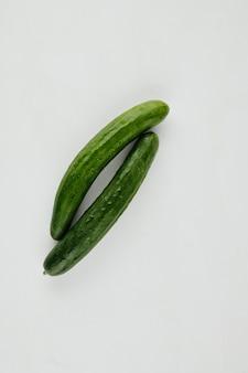ビタミンサラダ用に準備されたライトグレーのキッチンカウンターにある2つの長く熟したキュウリ