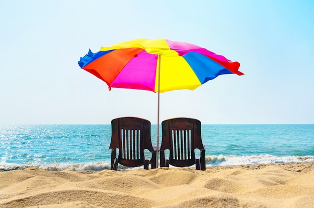Two lounge chairs under an umbrella on the beach