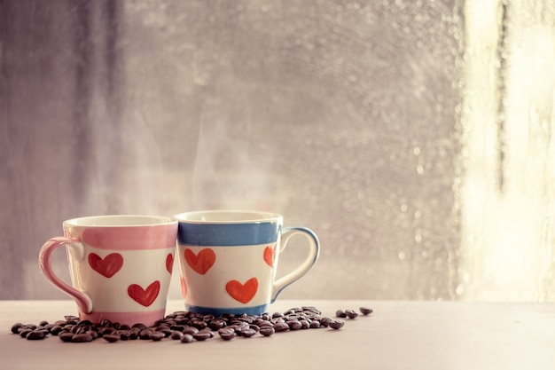 Two lovely cups with coffee bean on rainy day window background. vintage color tone